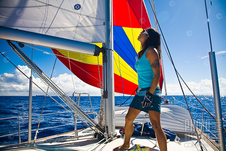 A young Asian woman checks the mainsail and spinnaker while cruising on a yacht off the shores of Oahu