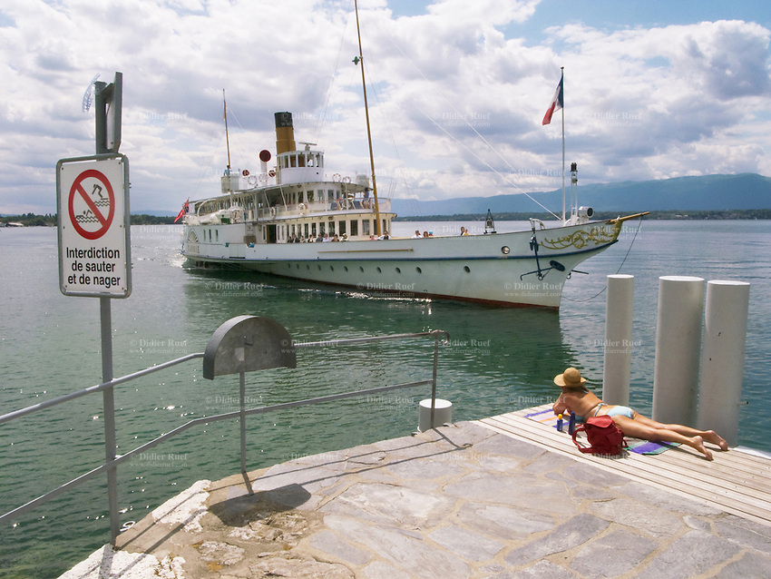 Switzerland. Canton Geneva. Anières. An old woman is sunbathing near the lake Geneva. The boat Savoie is mooring alongside the wharf of Anières. The Savoie is one of eight paddle wheel steamers, owned and ran by the Compagnie Générale de Navigation sur le lac Léman (CGN). The ship was built in 1914 during the Belle Époque's time  a period in European social history that began during the late 19th century and lasted until 1914. A sign prohibits to swim and jump in the water. 10.07.09 © 2009 Didier Ruef