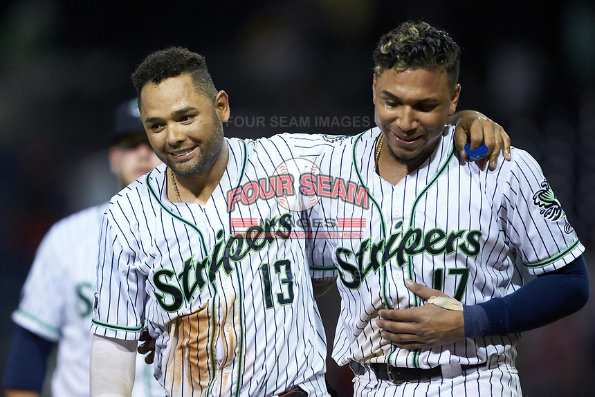 Andres Blanco (13) and Johan Camargo (17) of the Gwinnett Stripers celebrate following Blanco's walk-off walk against the Scranton/Wilkes-Barre RailRiders at BB&T BallPark on August 17, 2019 in Lawrenceville, Georgia. The Stripers defeated the RailRiders 8-7 in eleven innings. (Brian Westerholt/Four Seam Images)
