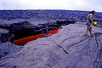 A geologist from the USGS takes and records lava samples at Volcanoes National Park on the Big Island of Hawaii.