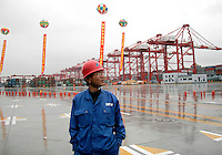A dock worker standing in the loading area of the just completed Yangshan Deep Water Port in Shanghai, China. ©Qilai Shen/Sinopix