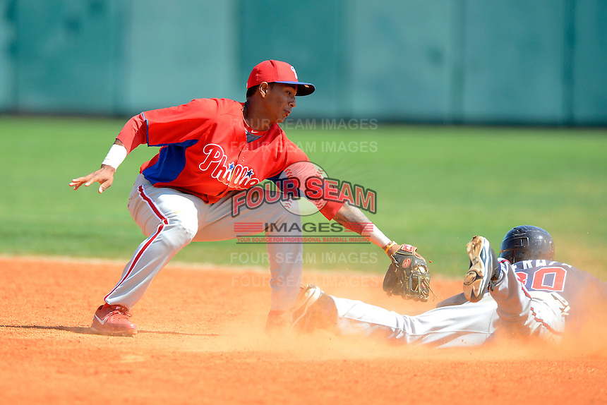 Philadelphia Phillies infielder Angelo Mora (28) tries to tag Jose Peraza (30) sliding in during a minor league Spring Training game against the Atlanta Braves at Al Lang Field on March 14, 2013 in St. Petersburg, Florida.  (Mike Janes/Four Seam Images)