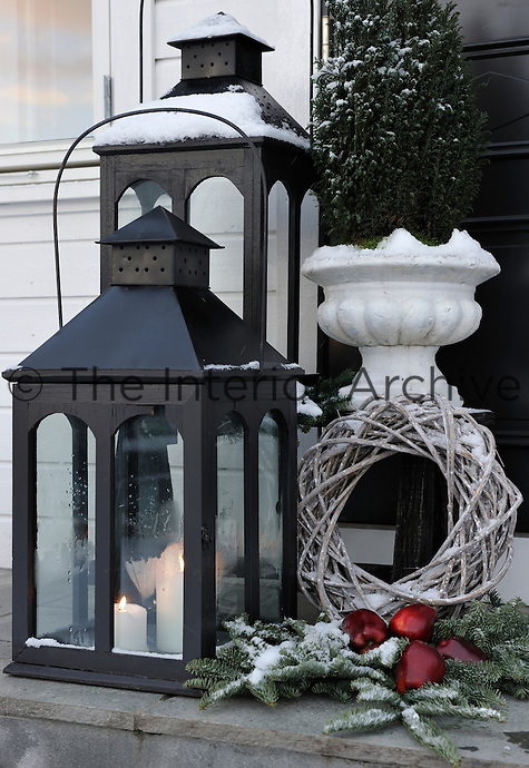 Large lanterns, spruce branches and a wreath begin the Christmas cheer before even entering the house