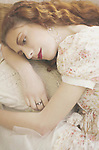 Girl with red hair wearing summer floral dress and white earrings relaxing with thoughtful expression on pillows