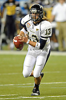 26 December 2010:  FIU quarterback Wesley Carroll (13) scrambles in the fourth quarter as the FIU Golden Panthers defeated the University of Toledo Rockets, 34-32, to win the 2010 Little Caesars Pizza Bowl at Ford Field in Detroit, Michigan.