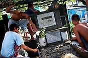 Young people are seen breaking the tomb to accommodate another family member in the same tomb at the Manila North Cemetery in Manila, Philippines. The scarcity of land and ever growing population has led the local filipinos to live in the same space around the graveyards in the Cemetary. Photo: Sanjit Das