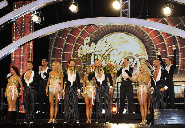 Strictly Professional Dancers <br /> The red carpet launch for 'Strictly Come Dancing' at Elstree Studios, Borehamwood, England.<br /> September 3rd, 2013<br /> full length gold dress black suit pinstripe trousers dancing holding hands <br /> CAP/FIN<br /> &copy;Steve Finn/Capital Pictures