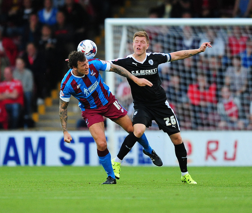 Scunthorpe United's Darius Henderson vies for possession with Barnsley's Alfie Mawson<br /> <br /> Photographer Chris Vaughan/CameraSport<br /> <br /> Football - Capital One Cup First Round - Scunthorpe United v Barnsley - Tuesday 11th August 2015 - Glanford Park - Scunthorpe<br />  <br /> &copy; CameraSport - 43 Linden Ave. Countesthorpe. Leicester. England. LE8 5PG - Tel: +44 (0) 116 277 4147 - admin@camerasport.com - www.camerasport.com