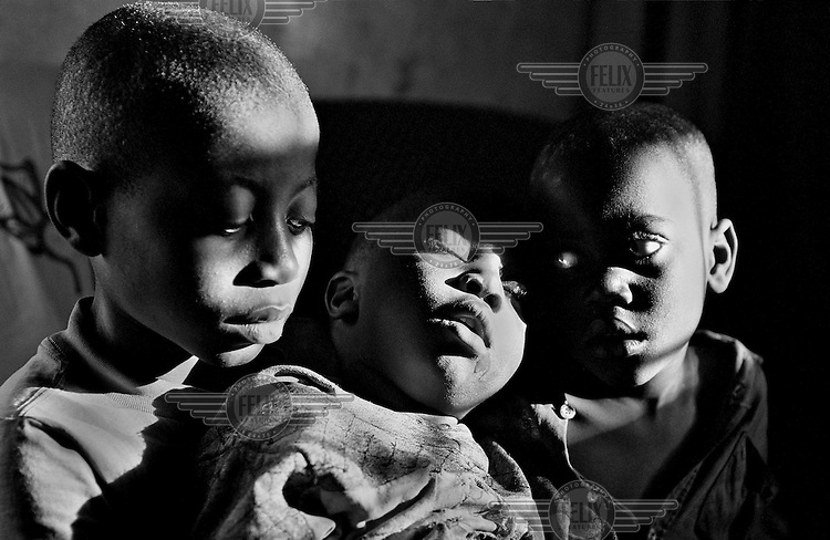 A very sick young boy is cared for by his brothers in Kitwe, Zambia on May 13, 2001. The brothers are among the more than 13 million African children who have been orphaned by the the AIDS pandemic. Worldwide, more than 20 million people have died since the first cases of AIDS were identified in 1981.