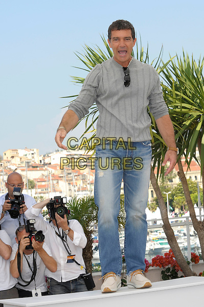 ANTONIO BANDERAS.'The Skin I Live In' photocall (La piel que habito) 64th International Cannes Film Festival, France.19th May 2011.full length grey gray top jeans denim funny mouth open standing on platform.CAP/PL.©Phil Loftus/Capital Pictures.