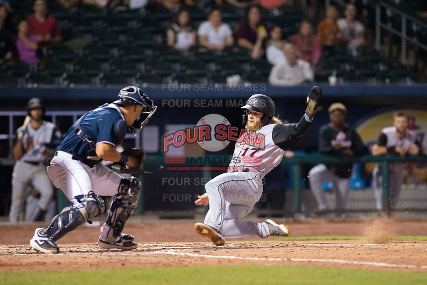 Arkansas Travelers outfielder Jake Fraley (17) slides into home ahead of the tag attempt from Northwest Arkansas Naturals catcher Nate Esposito (7) during a Texas League game between the Northwest Arkansas Naturals and the Arkansas Travelers on May 30, 2019 at Arvest Ballpark in Springdale, Arkansas. (Jason Ivester/Four Seam Images)