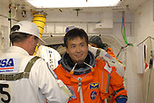 Cape Canaveral, FL - January 21, 2009 --  In the White Room on Launch Pad 39A at NASA's Kennedy Space Center in Florida, STS-119 Mission Specialist Koichi Wakata is helped by the Closeout Crew to put on his harness. The White Room provides access into space shuttle Discovery. Wakata and other crew members will conduct a simulated launch countdown as part of the prelaunch preparation known as Terminal Countdown Demonstration Test. The TCDT also includes equipment familiarization and emergency egress training. Discovery is targeted to launch on the STS-119 mission February 27, 2009. During the 14-day mission, the crew will install the S6 truss segment and solar arrays to the starboard side of the International Space Station, completing the station's truss, or backbone. .Credit: Jim Grossman - NASA via CNP