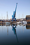 Large blue industrial crane reflection in water of Wet Dock marina, Ipswich, Suffolk, England