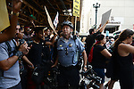 A police officer on State Street at Lake Street stops blocking the way for demonstrators supporting a Citizens Police Accountability Council to provide civilian oversight of the Chicago Police Department in Chicago, Illinois on July 11, 2016.  The demonstration attracted a larger crowd on the heels of last week's racially charged police shootings captured on video of Alton Sterling in Baton Rouge, Louisiana and Philando Castile in the St. Paul suburb of Falcon Heights, Minnesota which was followed by a mass shooting of five police officers by Afghan War veteran Micah Johnson who supported radical and violent black nationalist ideology.