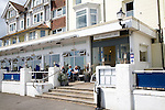 Brudenell Hotel, Aldeburgh, Suffolk, England. People enjoying morning coffee on the hotel terrace looking out over the sea.