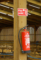 Fire extinguisher in a wooden lambing shed.