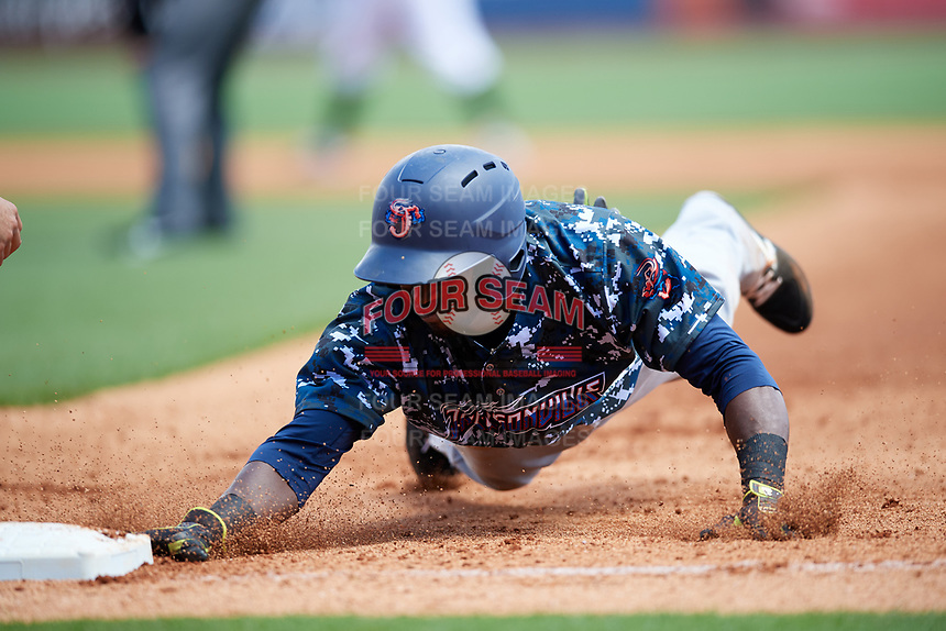 Jacksonville Jumbo Shrimp left fielder Jeremias Pineda (20) dives back to first base during a game against the Birmingham Barons on April 24, 2017 at Regions Field in Birmingham, Alabama.  Jacksonville defeated Birmingham 4-1.  (Mike Janes/Four Seam Images)