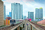 The Metrorail or Metro in downtown Miami is a rapid transit system that serves the urban centers of Miami and the Miami International Airport. The two trains seen here are arriving and departing the Government Center station. The tracks of the automated Metromover can be seen below the Metro tracks.