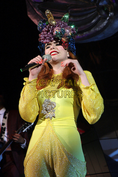 PALOMA FAITH.Performing live at The O2 Shepherd's Bush Empire, London, England..March 29th, 2010.stage concert live gig performance music half length yellow shiny catsuit jumpsuit playsuit harem singing fruit red nail varnish polish pink brooch.CAP/MAR.© Martin Harris/Capital Pictures.
