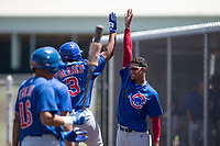Chicago Cubs shortstop Luis Vazquez (1) high gives Gustavo Polanco (3) during an Extended Spring Training game against the Los Angeles Angels at Sloan Park on April 14, 2018 in Mesa, Arizona. (Zachary Lucy/Four Seam Images)