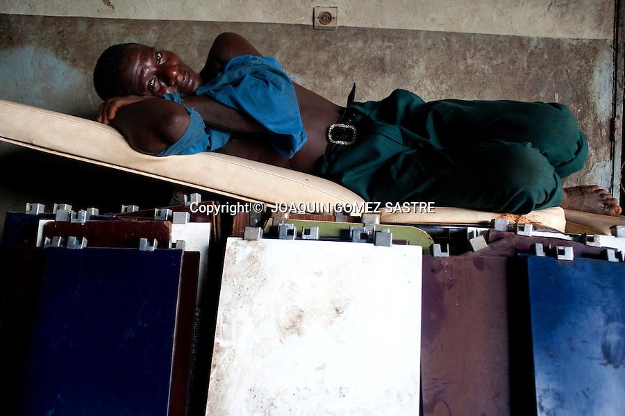 Un trabajador del hospital San Juan de Dios en Afagnan descansa encima de un monton de muebles viejos .foto ©  JOAQUIN GOMEZ SASTRE