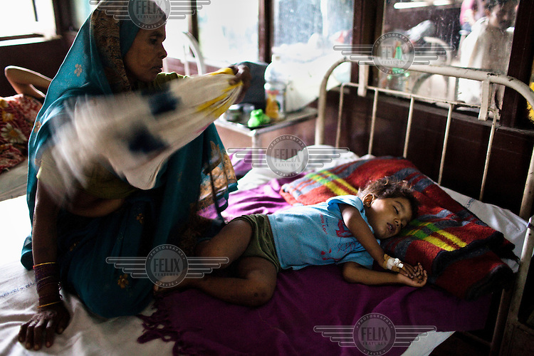 A woman covers her sick grandson with a blanket as he sleeps on a bed in the pediatric ward at Maharani Laxmibai Medical College in Jhansi.