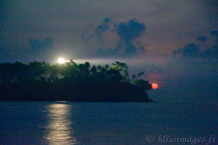 A red, full moon sinks into the horizon as Barberyn (Beruwala) light shines into the fading darkness and the approaching dawn. -near Bentota, Sri Lanka