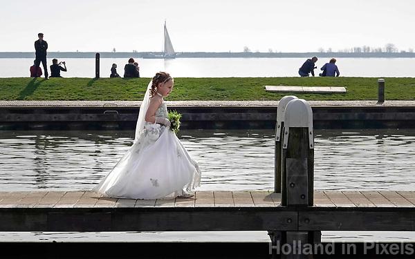 Nederland - Volendam - 2018.  Eerste communie in Volendam. Na de kerkdienst loopt een meisje in haar witte jurk op een steiger in de haven.  Foto Berlinda van Dam / Hollandse Hoogte