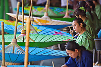 Artists hand painting decorative umbrellas in village of Bo Sang, near Chiang Mai, Thailand