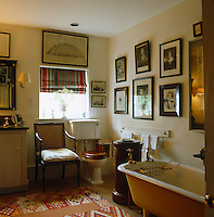 A cane-backed chair is placed beside the toilet in this bathroom with walls covered in antique prints