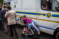 JOHANNESBURG, SOUTH AFRICA - DECEMBER 07: A girl rests on a stroller as a Police officer stands guard, as people gather to pay respect and tribute to former President Nelson Mandela outside his Houghton home on December 7, 2013 in Johannesburg, South Africa. Mr Mandela, died on Thursday aged 95, spent 27 years in jail before becoming South Africa's first black president in 1994.<br /> Photo by Daniel Berehulak for The New York Times