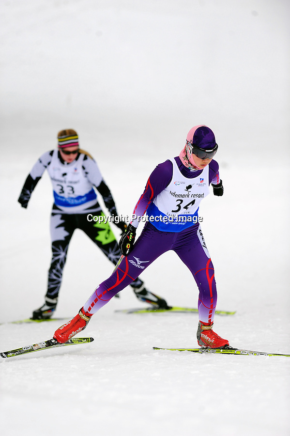 Shoko Ota of Team Japan competes in the BT Women standing sprint during the 2013 International Paralympics Nordic Skiing World Cup in Cable, WI. Behind her is Erica Noonan of Tam Canada.
