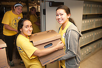 Katie Simoniello,'20, Melanie Morales,'20, and Mikayla Anderson,'20, move boxes of magazines to a storage area at the Redwood Library in Newport as they take part in Salve's Exploration Day of Service