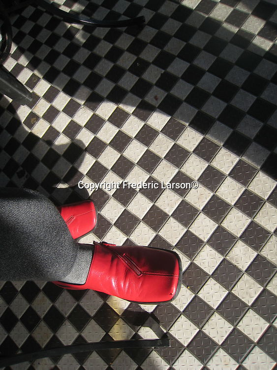 A red shoe accents the checkered board tiles in a café in North Beach, San Francisco, California.