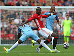 Paul Pogba of Manchester United tackled by Fernandinho and Fernando of Manchester City during the Premier League match at Old Trafford Stadium, Manchester. Picture date: September 10th, 2016. Pic Simon Bellis/Sportimage
