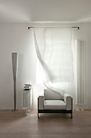A De Padova design armchair is flanked by a pair of radiators of differing sizes, the standard lamp is by Foscarini and the gauze curtain by Bab Anmil