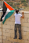 A Palestinian youth climbs a wall in order to place a Palestinian flag in a position overlooking Israeli soldiers during a non-violent demonstration against Israel's controversial separation barrier in the West Bank town of Beit Jala, near Bethlehem on 11/07/2010.