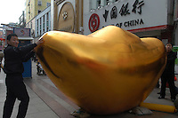 People touching a model of gold ingot in front of a branch of the Bank of China in Nanchang, China.   .