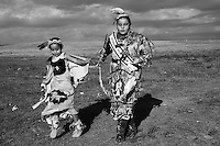 Rhiannon Frazier and her sister, Michel playing on the fields next to their trailer. The girls, grand grand daughters of Chief Red Cloud are dressed with national costumes hand made by their mother. Their mother, like many others, is unemployed and makes her living selling jewelry she makes from porcupine quills. Unemployment on the Reservation exceeds 78% and 97% of families live below the Federal poverty level. Rhiannon has participated in the regional veteran Pow Wow for 5 years and has won 17 trophies. In 2007 she has been chosen as the Veteran's Pow Wow queen.