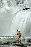 08945-C. An angler casts a fly for trout at the base of Lower Mesa Falls on the Henry's Fork of the Snake River, Idaho.