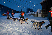 Volunteer dog handlers help Aliy Zirkle get from her parking spot to the trail after her 24 hour layover at Takotna during Iditarod 2009