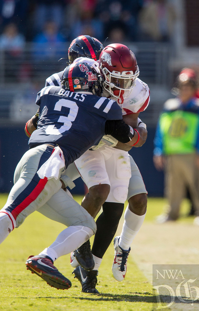 Hawgs Illustrated/BEN GOFF <br /> T.J. Hammonds, Arkansas running back, tries to break the tackle of D.D. Bowie, Ole Miss cornerback, and DeMarquis Gates (3), Ole Miss linebacker, on a run in the third quarter Saturday, Oct. 28, 2017, at Vaught-Hemingway Stadium in Oxford, Miss.
