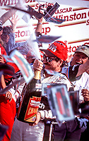 Dale Earnhardt celebrates with champagne after winning the Winston 500 and collecting a million dollar bonus from Winston at Talladega Superspeedway, In Talladega, Alabama, October 15, 2000.  It would be the final win of his career.  (Photo by Brian Cleary/bcpix.com)