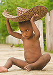 Young boy plays with a big hat, Lobo Village, Papua.