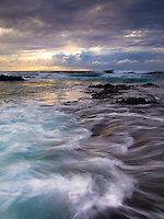 At sunset, waves collide against each other along the coastline of Pine Trees Beach on the Big Island.