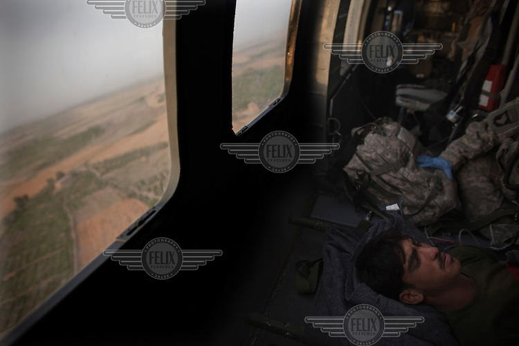 An Afghan National Army (ANA) soldier who was injured in an IED (improvised explosive device) blast, is treated on board a US Army medevac helicopter during a rescue mission.