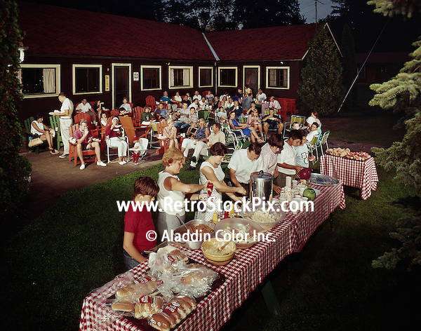 Family lining up at buffet table for a BBQ in 1965.