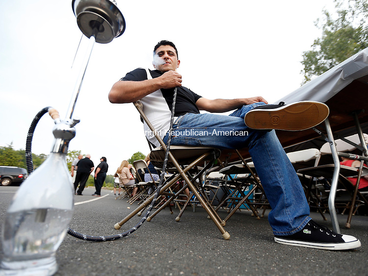 Waterbury, CT- 12 June 2015-061215CM04- Fares Hayek from Berlin, smokes from a hookah during the annual Taste of Lebanon festival in Waterbury on Friday.  The event held at Our Lady of Lebanon Church continues Saturday from 12 p.m. to 12 a.m.  Christopher Massa Republican-American