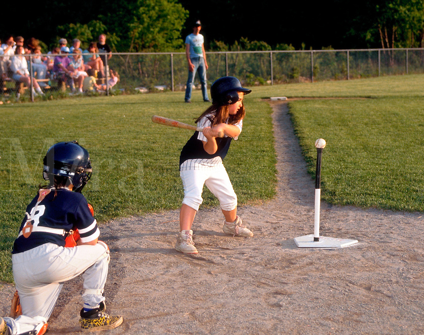 Children playing T-ball, young girl at bat.