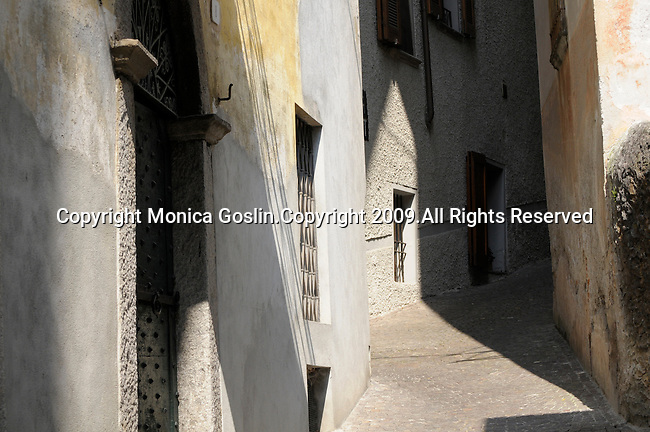 A narrow and steep street with sunlight in Gravedona, a town on Lake Como, Italy.